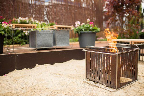 Der Sandkasten bietet auch Platz für eine mobile Feuerstelle