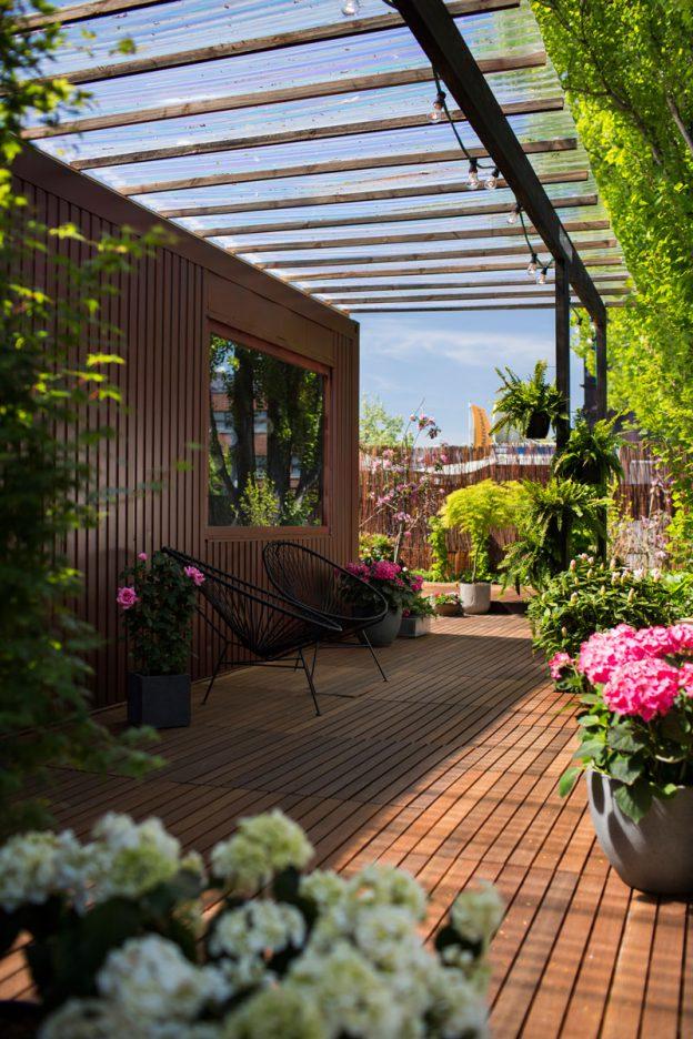 Schicker Freisitz: Die Terrasse mit Holzboden, Pergola und leichten Metallmöbeln