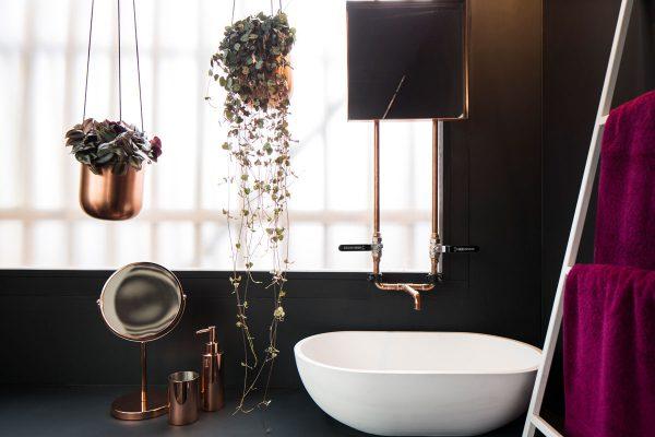 Das kleine Duschbad mit weißem Handwaschbecken und Elementen aus Kupfer