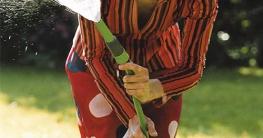 Frau spielt mit Wasserschlauch