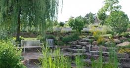 Wer sich mediterranes Flair hinter dem Haus wünscht, sollte auf Kräuter und Duftpflanzen setzen, wie Lavendel, Rosmarin oder Thymian. Daneben geben Natursteine dem Garten südländisches Flair.